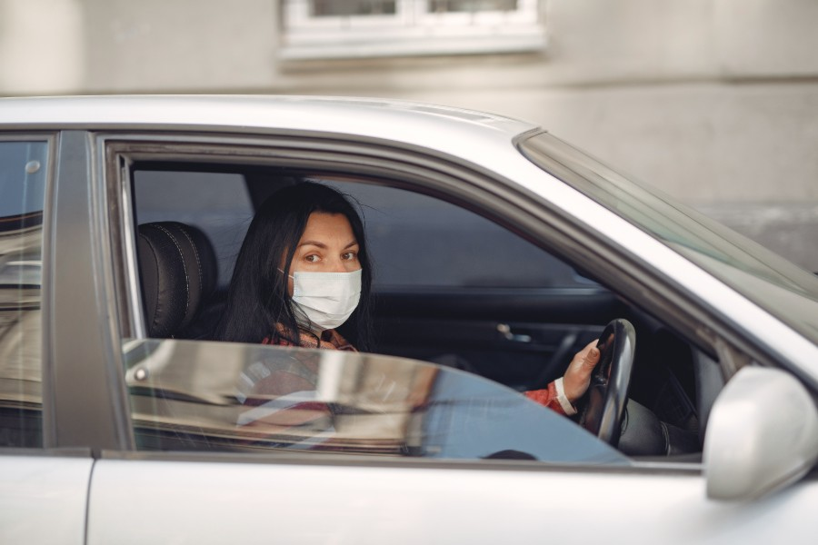 Woman driving a car wearing a mask